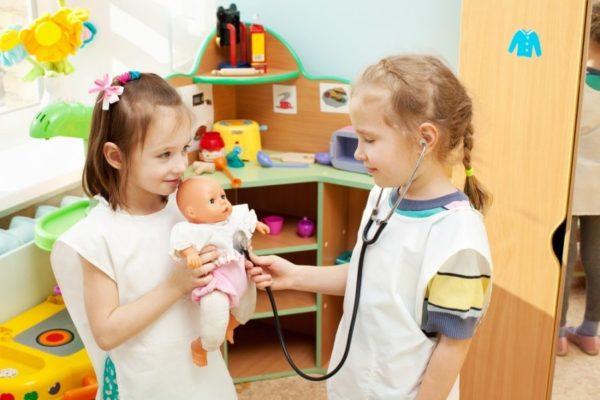 Две девочки играют в больницу с куклой