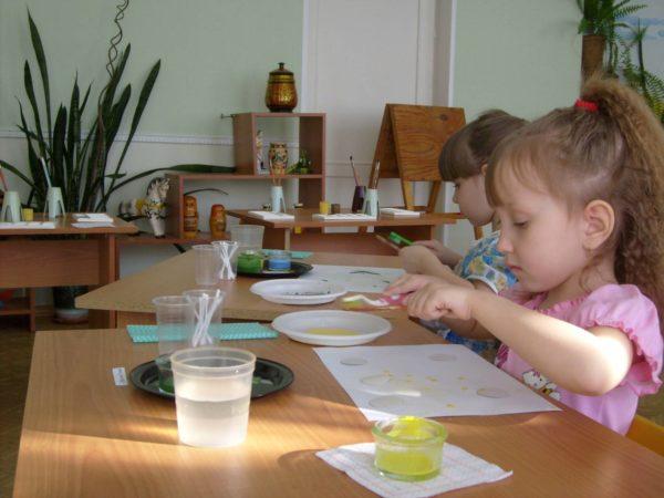 Две девочки проводят опыты с водой и красками