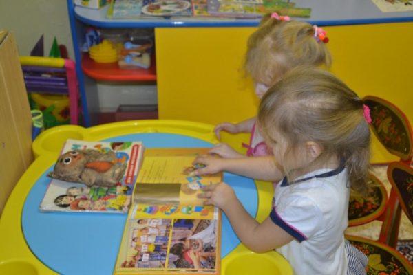 Две девочки рассматривают альбом с фотографиями и картинками, на открытой книжке лежит Чебурашка