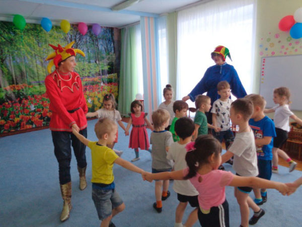 Две воспитательницы в костюма скоморохом ведут хоровод в детьми