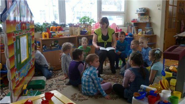Воспитатель с книгой на коленях беседует со старшими дошкольниками