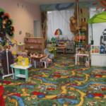 Группа в детском саду, на левой стене павлин, справа синие столы и стулья