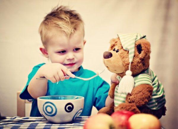 Мальчик кормит плюшевого мишку