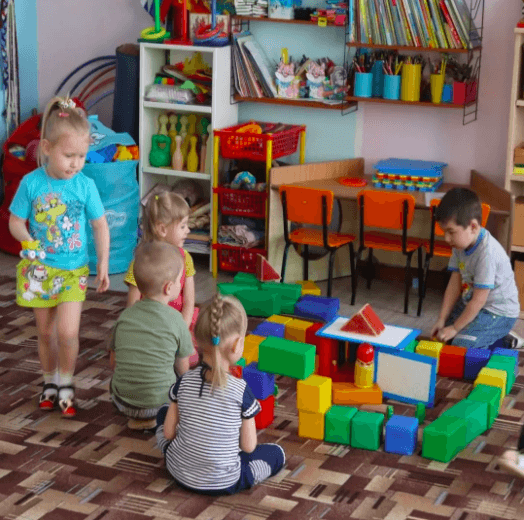 Дошкольники играют с постройкой из деталей крупного конструктора