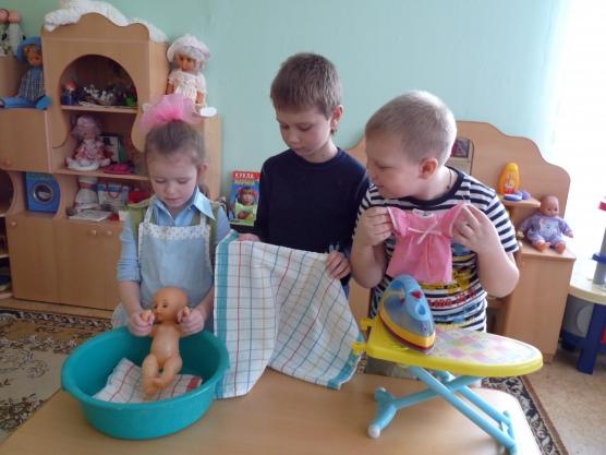 Два мальчика и девочка играют в семью