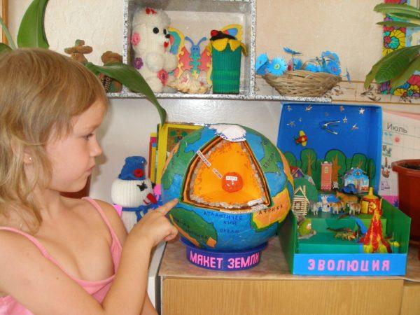 Девочка изучает макет Земли