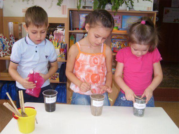 Трое детей изучают свойства песка, земли и глины