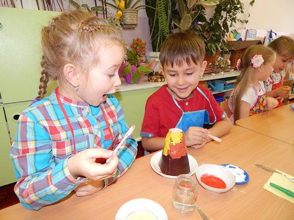 Мальчик и девочка проводят эксперимент с макетом вулкана