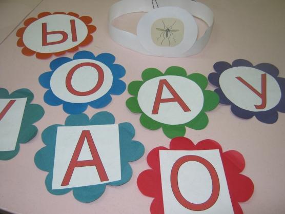 Карточки с гласными буквами приклеены на разноцветные цветочки