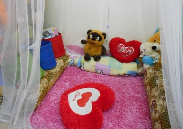 Коврик и мягкие игрушки внутри уголка уединения