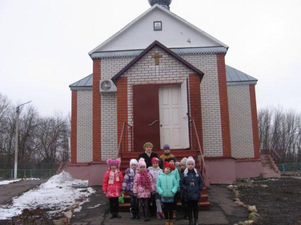 Дети и педагог стоят перед входом в храм