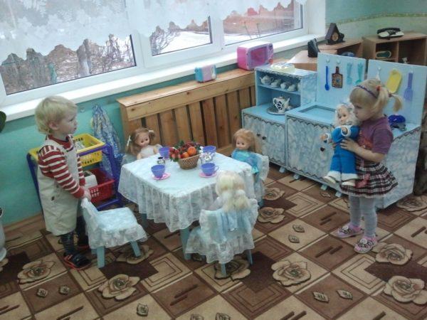 Двое детей играют в чаепитие с куклами
