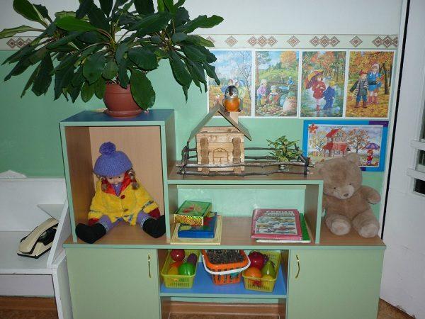 Кукла в осенней одежде в ящике стола слева, плюшевый медведь справа