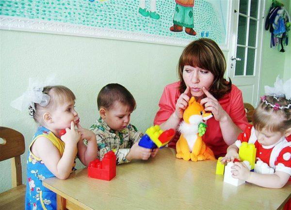Педагог показывает детям, как выполнять артикуляционное упражнение