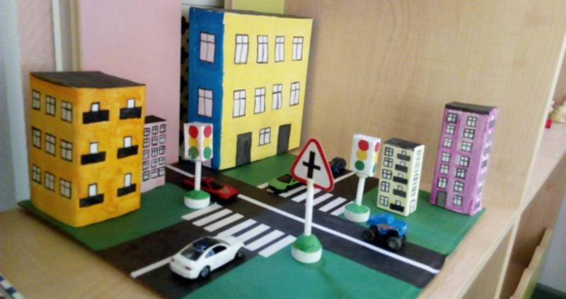 Макет улицы с перекрёстком, дорожными знаками, светофором и белой игрушечной машинкой