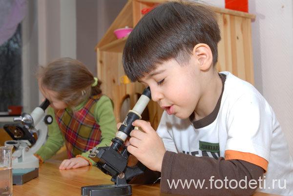 Мальчик и девочка работают с микроскопами
