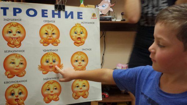 Мальчик показывает своё настроение на плакате с изображениями различных эмоций