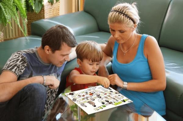 Мальчик вместе с мамой и папой размещает наклейки на листе, лежащем на стеклянном столике