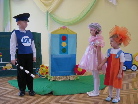 Мальчик в костюме инспектора ДПС что-то говорит девочкам в розовом и оранжевом платьях