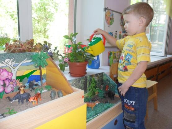 Мальчик в жёлтой футболке поливает из детской лейки цветы