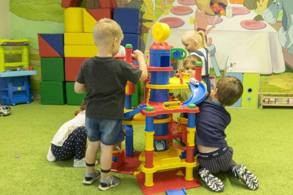 Мальчики строят фигуру из больших деталей конструктора