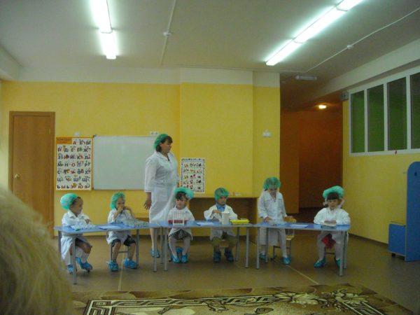 Дети и педагог в белых халатах проводят опыты