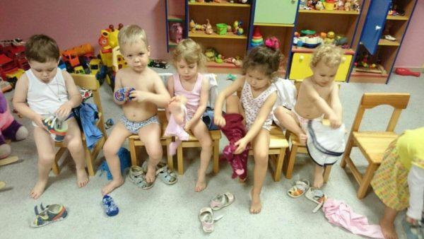 Малыши одеваются, сидя на стульчиках