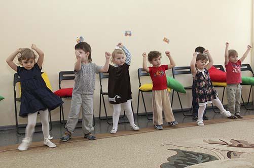 Младшие дошкольники играют в музыкальную подвижную игру