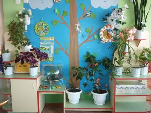 На стене на синем фоне приклеено большое бумажное дерево, на небольших белых столах — цветы в белых горшках