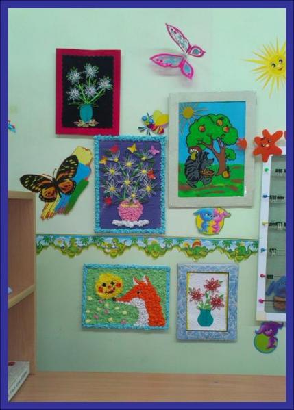 На стене висят детские работы, выполненные в различных техниках