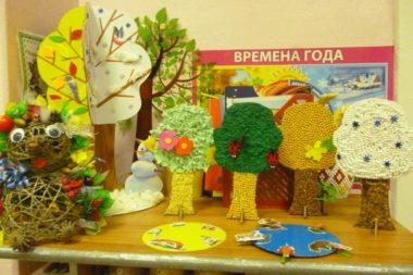На столе стоят макеты деревьев в разное время года, слева поделка из верёвки