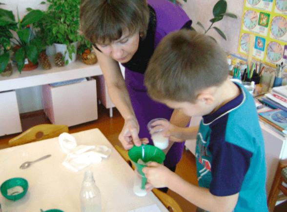 Педагог помогает мальчику провести опыт с водой