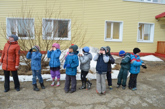 Дети и педагог наблюдают за солнцем на прогулке