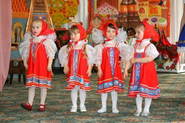 Четыре девочки в костюмах исполняют народный танец