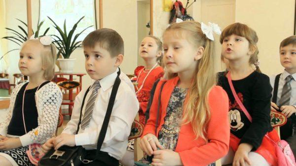 Нарядно одетые дети сидят на стульях, выставленных в ряды