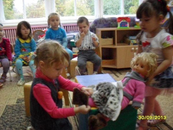Две девочки одевают куклу, остальные дети наблюдают
