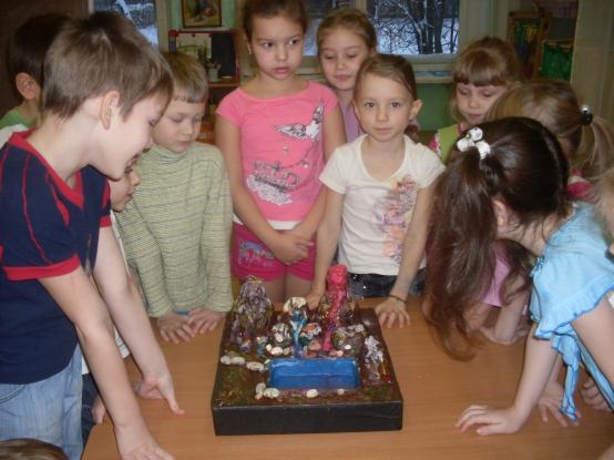 Группа детей изучает макет вулкана