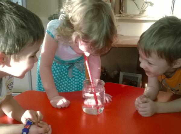 Трое детей проводят опыт «Буря в стакане»