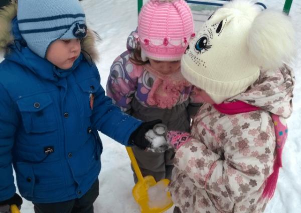 Трое детей рассматривают снег на прогулке