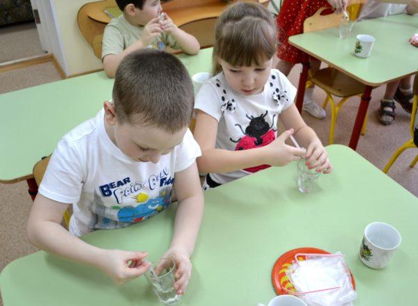 Дети, сидя за партами, проводят опыты с водой