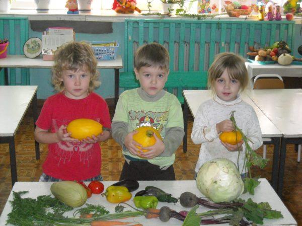 Трое детей держат в руках овощи, перед ними на столе лежат баклажаны, перец, кочан капусты, свёкла и др