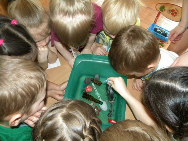 Дети склонились над тазом с водой, в котором находятся различные предметы