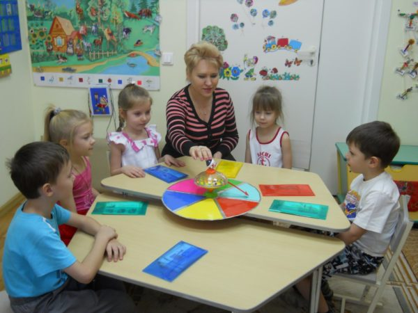 Дети и педагог, сидя за столом, играют в дидактическую игру