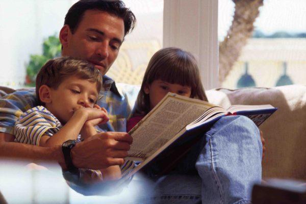 Мужчина читает книгу мальчику и девочке