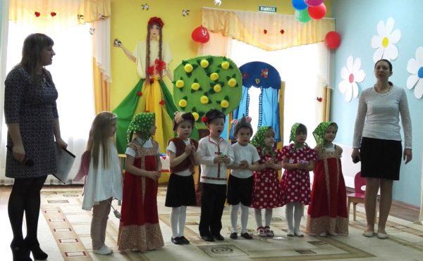 Дети в костюмах участвуют в представлении, педагоги стоят рядом