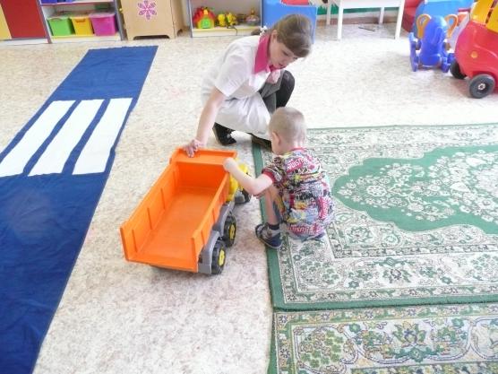 Педагог объясняет ребёнку устройство грузовой машины