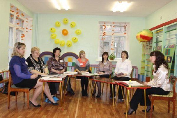 Педагоги сидят полукругом, воспитатель справа рассказывает, остальные слушают