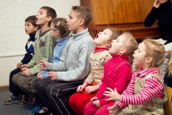 Дети поют, сидя на стульях