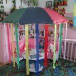Пляжный зонт с длинными лентами, установленный на маленьком столике
