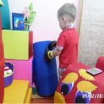Мальчик в боксёрских перчатках бьёт мягкий модуль